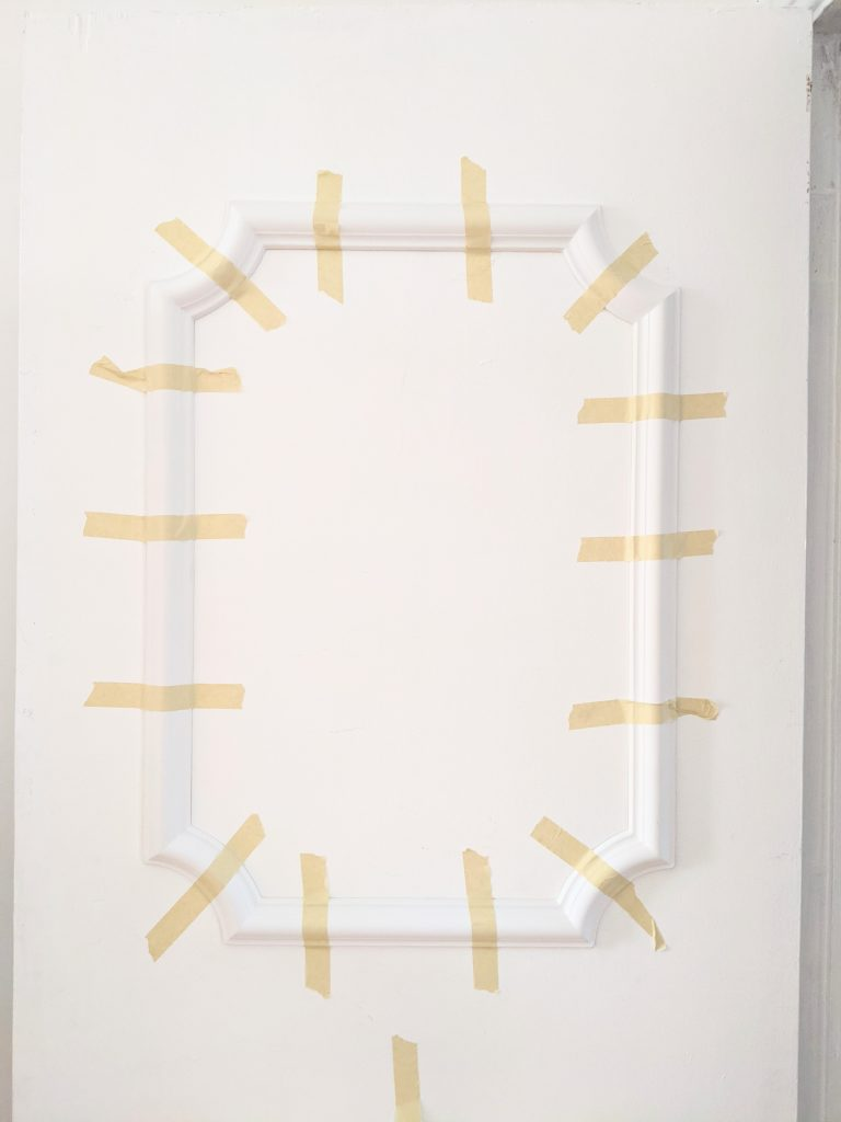 tape panel until glue dries DIY door makeover installing decorative trim moulding Montreal lifestyle fashion beauty blog